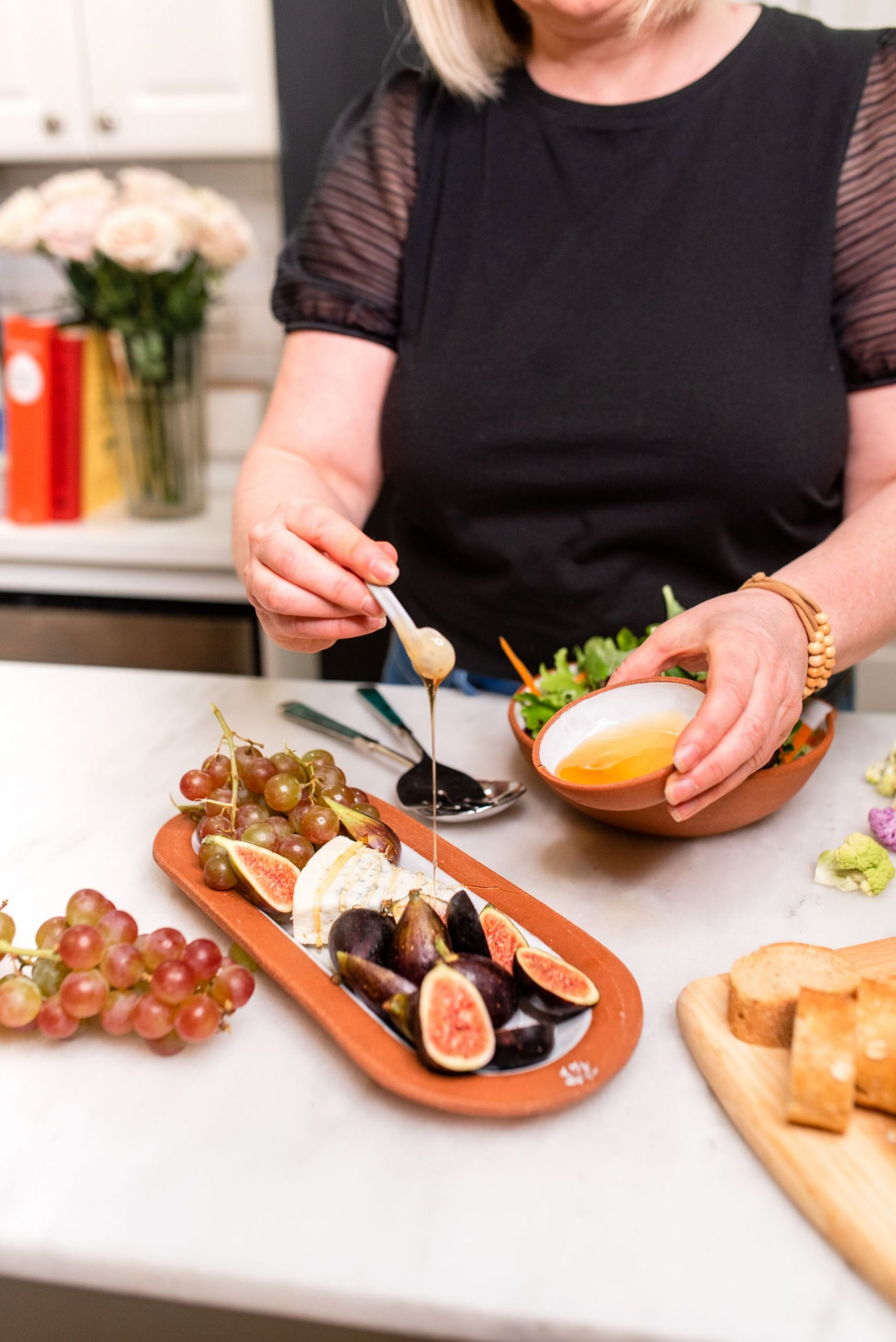 Learn the Basics of Photography - Woman drizzling honey over platter of figs, cheese, and grapes