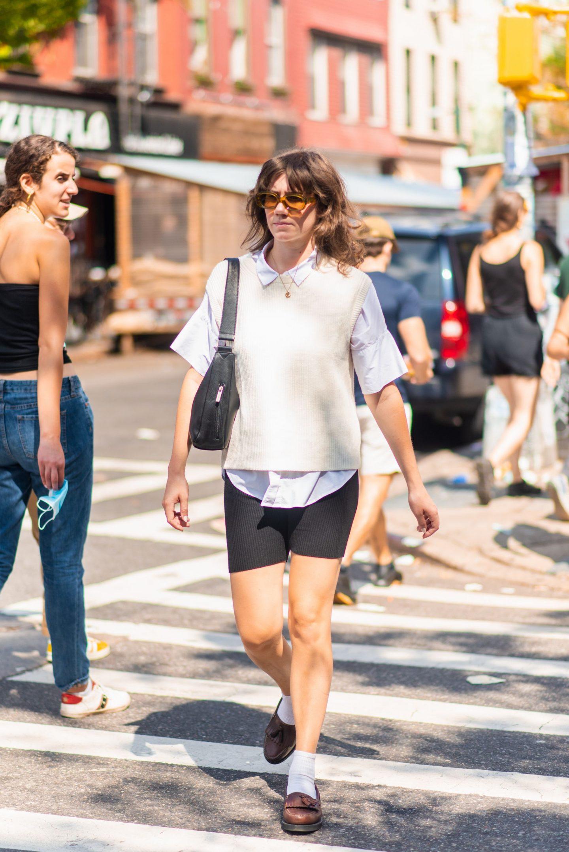 NYC street style fall outfit idea - woman wearing white sweater vest and black bike shorts - Karya Schanilec NYC fashion photographer
