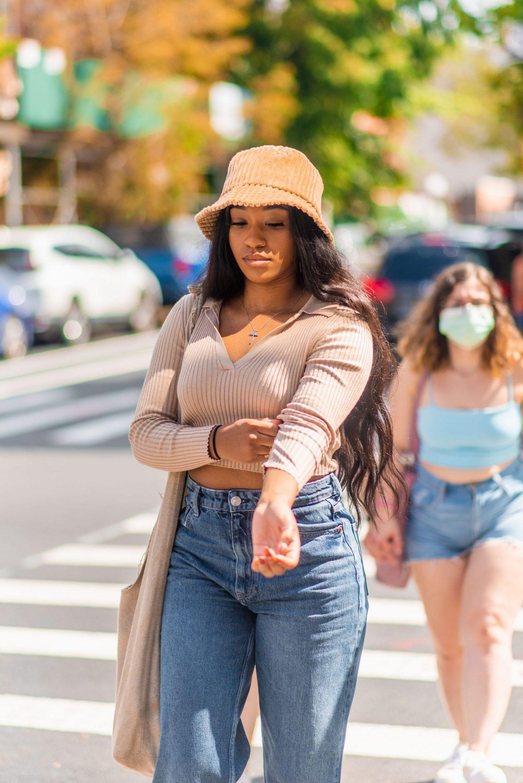 NYC street fashion fall outfit idea - woman wearing corduroy bucket hat and cropped knit sweater - Karya Schanilec NYC fashion photographer