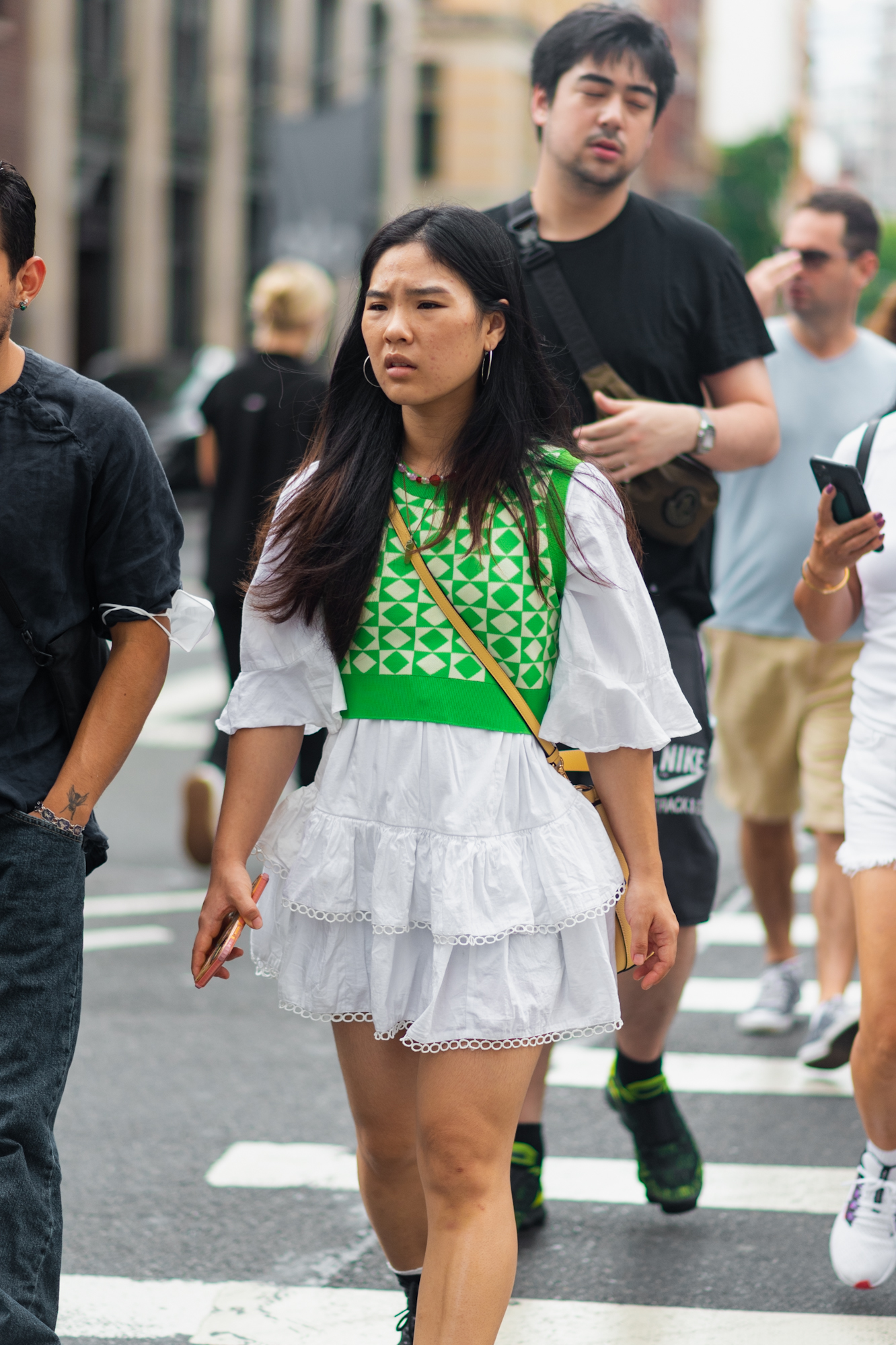 NYC street style fall outfit idea - woman wearing green sweater vest layered over frilled white dress in SoHo - Karya Schanilec NYC fashion photographer
