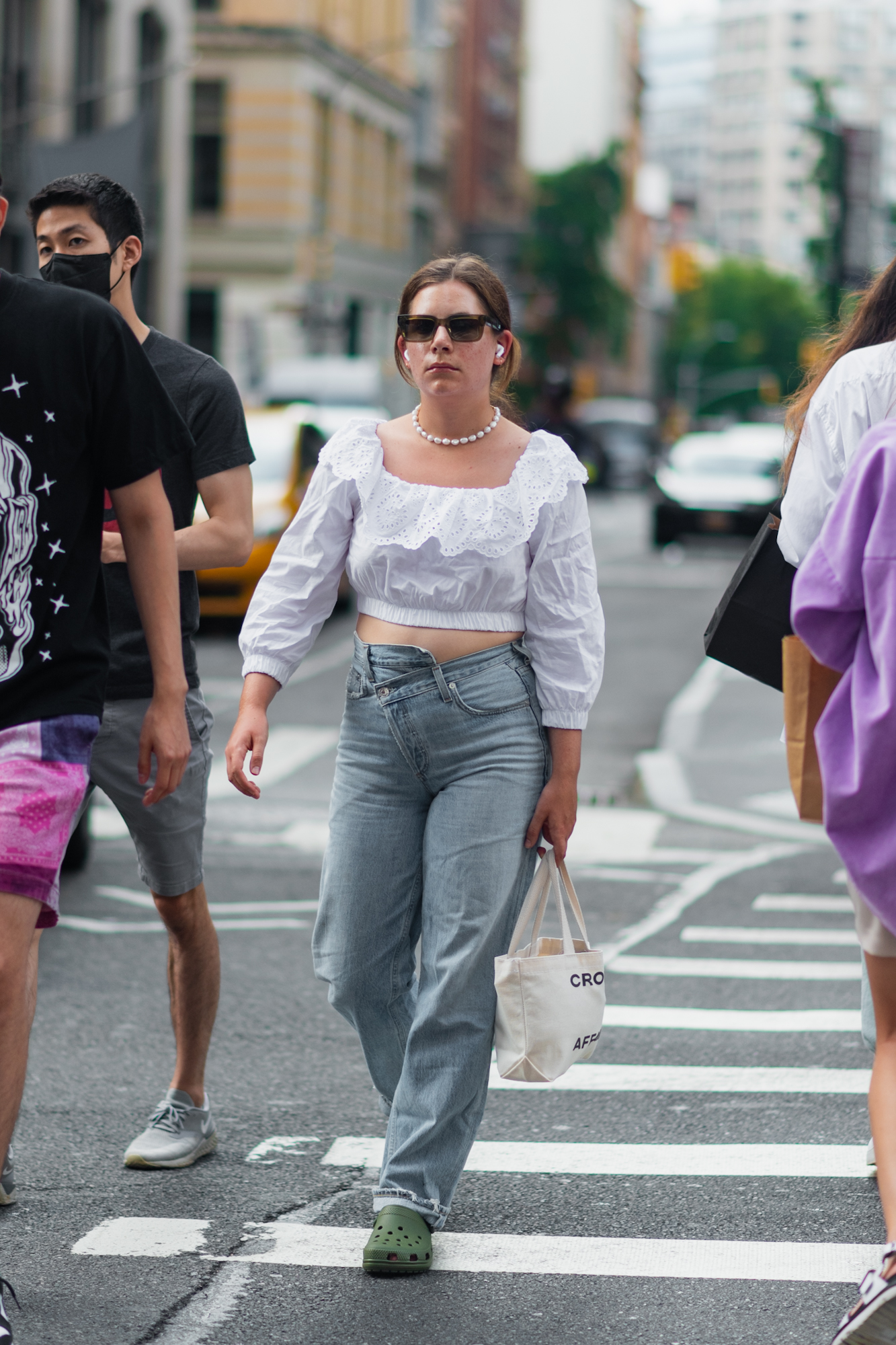 NYC street style fall outfit idea - woman wearing trendy white blouse and straight leg jeans in SoHo - Karya Schanilec NYC fashion photographer